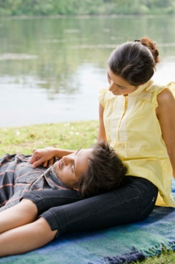 Stock Photo: 1557R-392098 Couple lying down in grass in park