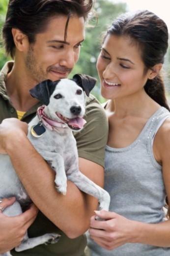 Couple holding dog : Stock Photo