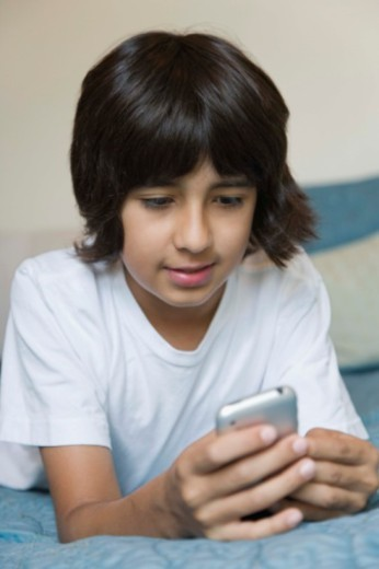 Stock Photo: 1557R-392270 Boy texting on cell phone