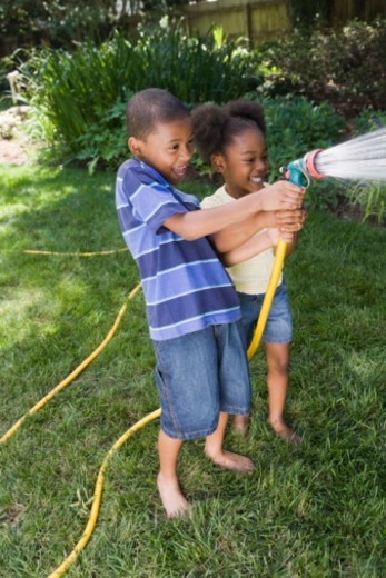 Children spraying water from hose : Stock Photo