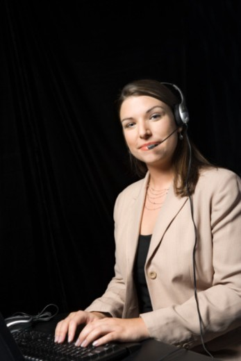 Woman wearing headset and typing : Stock Photo