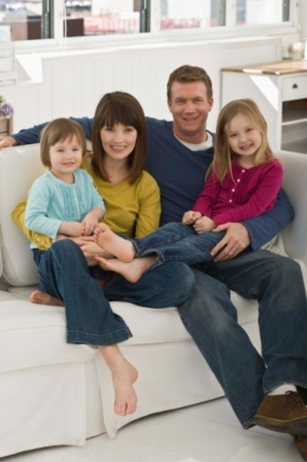 Portrait of family sitting on couch : Stock Photo