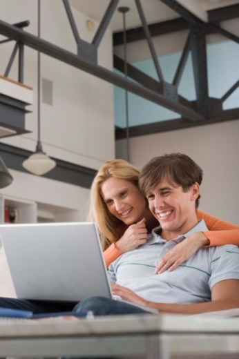 Couple with laptop embracing : Stock Photo