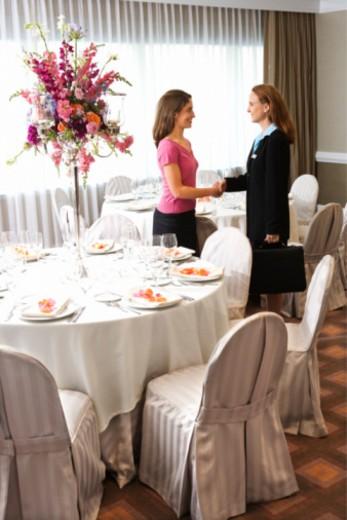 Women shaking hands in upscale restaurant : Stock Photo