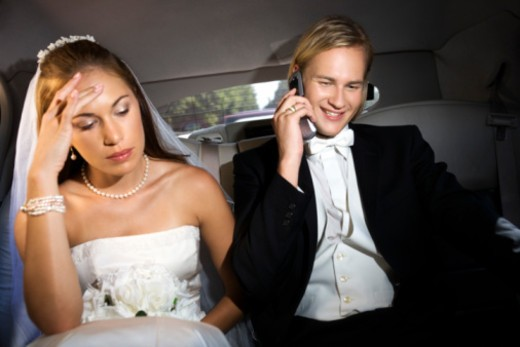Stock Photo: 1557R-395172 Bride annoyed at groom using cell phone