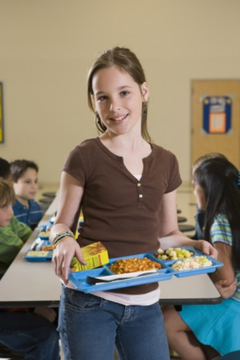 Girl standing in cafeteria with tray : Stock Photo