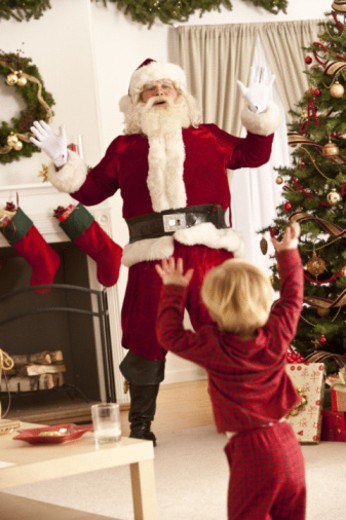 Young boy discovering Santa Clause on Christmas. : Stock Photo