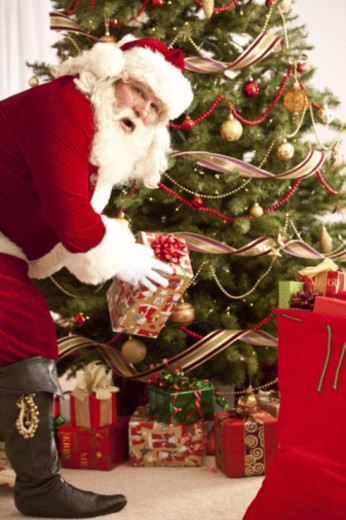 Santa Clause placing gifts under Christmas tree. : Stock Photo