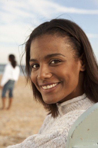 woman on the beach with friend int he background : Stock Photo