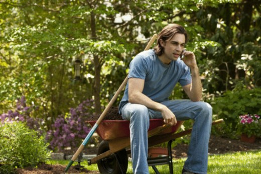 man sitting on wheel barrel on cell phone : Stock Photo