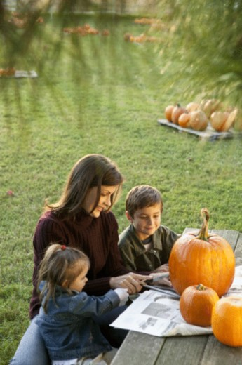 Mother with Children carving pumpkins : Stock Photo