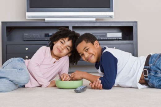 Children watching television with snack : Stock Photo