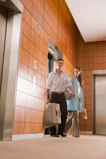 Couple holding hands and exiting elevator in hotel : Stock Photo