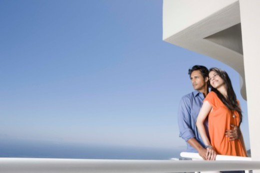 Stock Photo: 1557R-399559 Couple standing together on balcony of hotel room