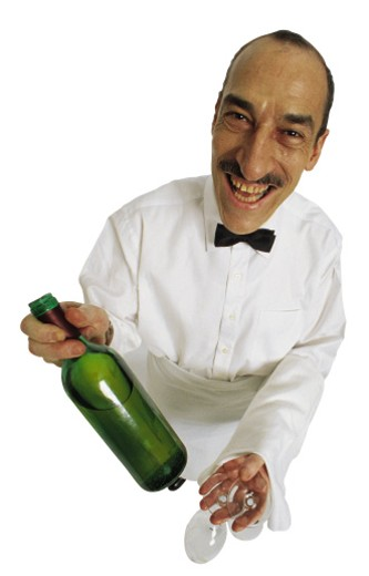 Steward with wine bottle and glass , grinning : Stock Photo