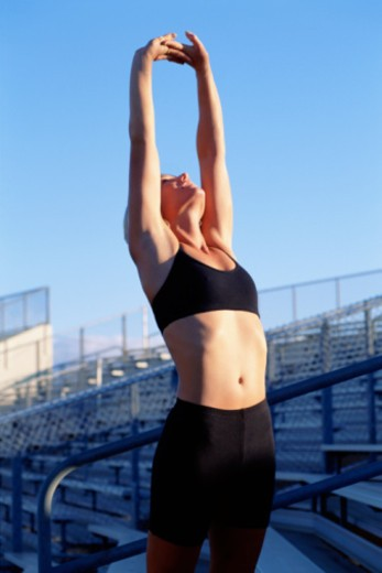 Woman stretching with arms over head, looking to sky : Stock Photo