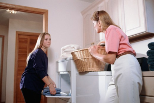 Stock Photo: 1557R-400843 Mother talking with pregnant teenage daughter in laundry room