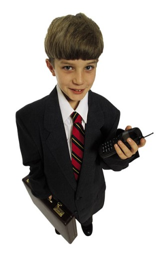 Boy dressed in businessman's clothes with cell phone : Stock Photo
