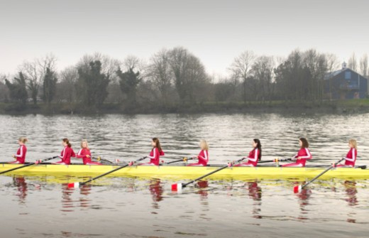 Stock Photo: 1557R-401205 Female rowers rowing scull, one rowing opposite direction, side view