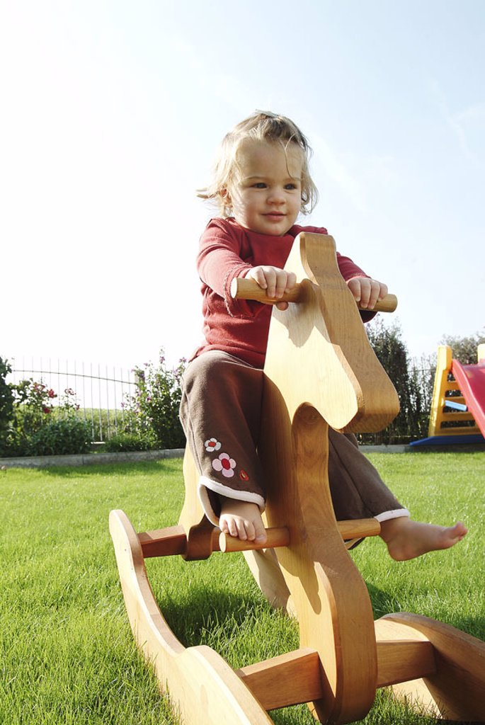Meadow, girls, nakedfoot, rocking horse,  sitting,   Child, toddler, 2-4 years, happily, happy, sunny, outside, leisure time, childhood, whole bodies, playing, game, activity, toy, wood horse, wood rocking horse, swings, garden, background, slide, : Stock Photo