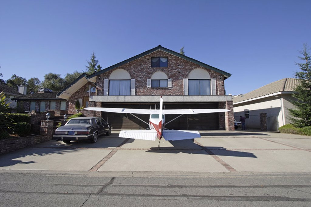 House, driveway, garage, entrance, car,  Private airplane, parks,   USA, California, Sacramento, Cameron park, garage entrance, private car, ´hangar´, airplane, engine airplane, propeller machine, transportations, unusually, American Way Of Life mobility : Stock Photo