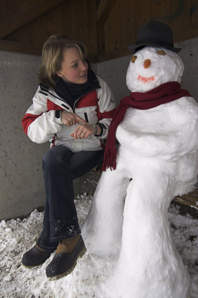 Bus stop, wood bank, snowman, Woman, young, gesture, watch, winters,   20-30 years, blond, winter clothing, sitting, stop, shelters, means of transportation publicly, waiting, wait, patience, punctuality, unpunctuality, departure, season, cold, frost, : Stock Photo