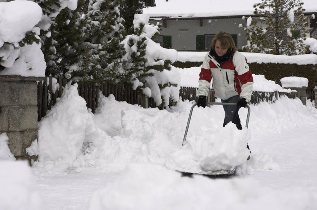 Stock Photo: 1558-101953 Woman, young, snow areas, winters,    Snow racketeers clear 20-30 years, blond, winter clothing, snow, snow shovel, snow witch symbol Räumdienst Räumpflicht Schneeräumdienst, Schneeräumpflicht, snow masses, snow chaos, winter break-in, snow shovels, effor