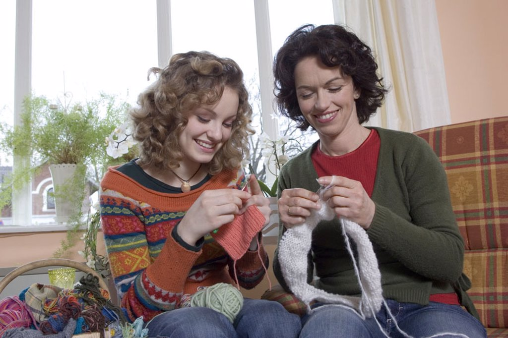 Mother, knitting, daughter, crochets, smiling,  Chairs, sitting,   Series, people, women, two, happy, blond, brunette, curls, teenagers, 15-20 years, parent, 30-40 years, leisure time, hobby, learning together, interest, shows, handicraft, skill, wool, pr : Stock Photo