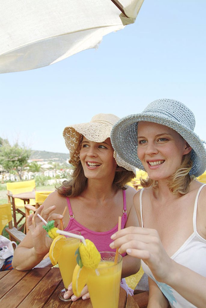 Women, young, sunhats, cocktail, beach-bar, semi-portrait, series, people, two, friends, sisters, 20-30 years, smiles, cheerfully, happy, summery, headgear, hats, outside, sunny, bar, cocktail-bar, pub, beach-cafe, table, sits, beverage, fruity, fresh, co : Stock Photo