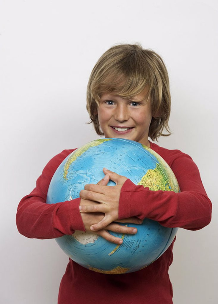 Give birth, globe, holds, smiles, gaze camera, semi-portrait, people, young, child, youth, 11 years, school, students, instruction, learning, joy, formation, knowledge, geography, countries, earth, continents, geography, geography-instruction, studio, get : Stock Photo