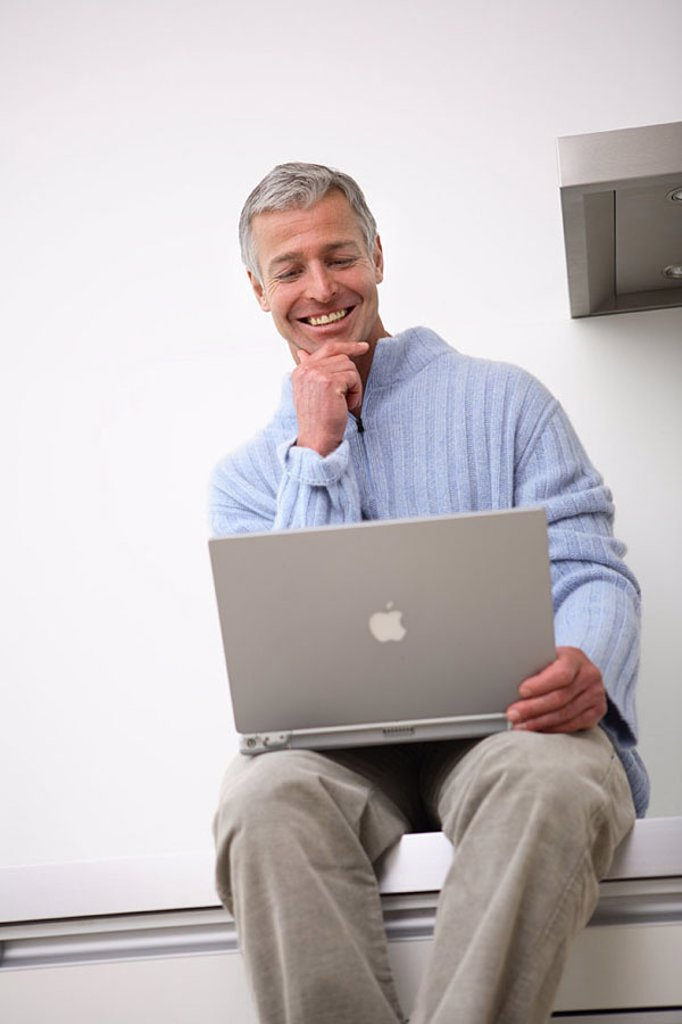 Stock Photo: 1558-113796 Man, laptop, kitchen-line, sits, no property release, people, 30-40 years, 40-50 years, grey-haired, smiles, cheerfully, nonchalant, casual, leisure time, hobby, Lifestyle, computers, data input, internet, Internetsurfen, internet-access, e-mail, chatten,