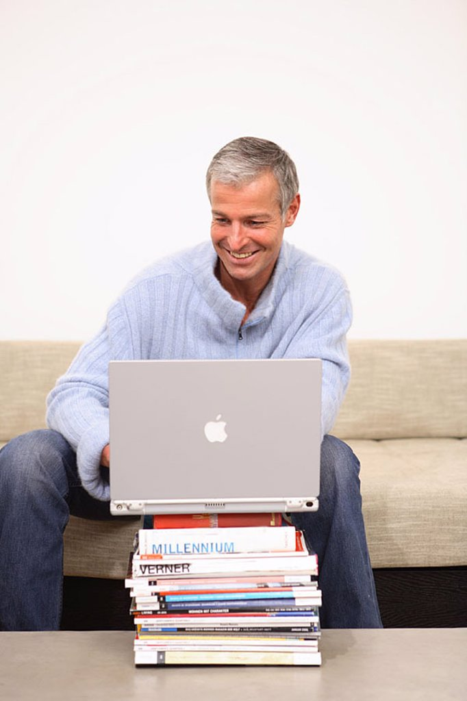 Stock Photo: 1558-113868 Man, smiles, laptop, data input, Bücherstapel, sofa, sits, no property release, series, people 40-50 years grey-haired, leisure time, Lifestyle, hobby, internet, internet-access, internetsufren, chatten, User, online, e-mail, communication, telecommunicat