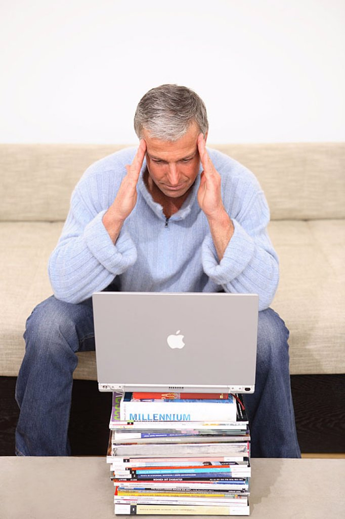 Man, gesture, headaches, laptop, Bücherstapel, sofa, sits, no property release, series, people 40-50 years grey-haired, leisure time, Lifestyle, hobby, internet, internet-access, internetsufren, chatten, User, online, e-mail, communication, telecommunicat : Stock Photo