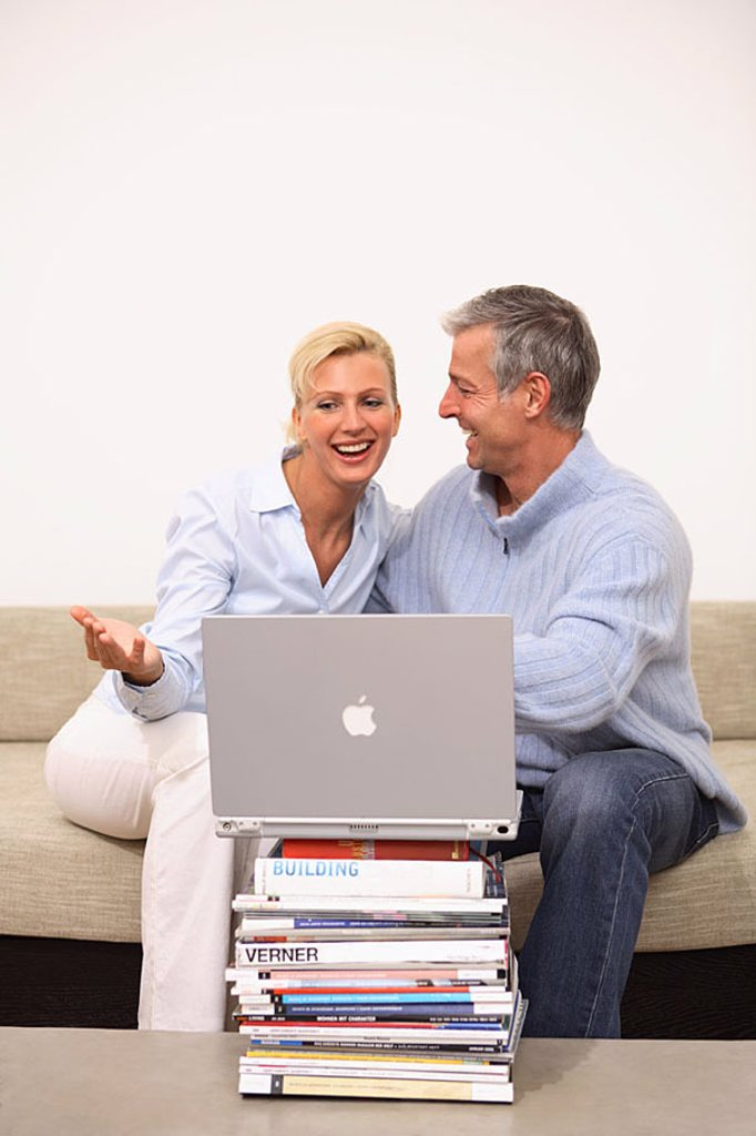 Mate, smiles, laptop, data input, Bücherstapel, sofa, sits, no property release, series, people 30-40 years 40-50 years, cheerfully, joy, fun, together, partnership, relationship, grey-haired, leisure time, Lifestyle, hobby, internet, internet-access, int : Stock Photo