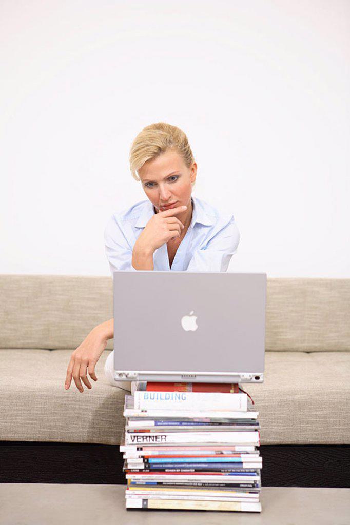Woman, seriously, laptop, Bücherstapel, sofa, sits, no property release, series, people, 30-40 years, blond, leisure time, Lifestyle, hobby, work, internet, internet-access, internetsufren, chatten, User, online, e-mail, communication, telecommunication, : Stock Photo