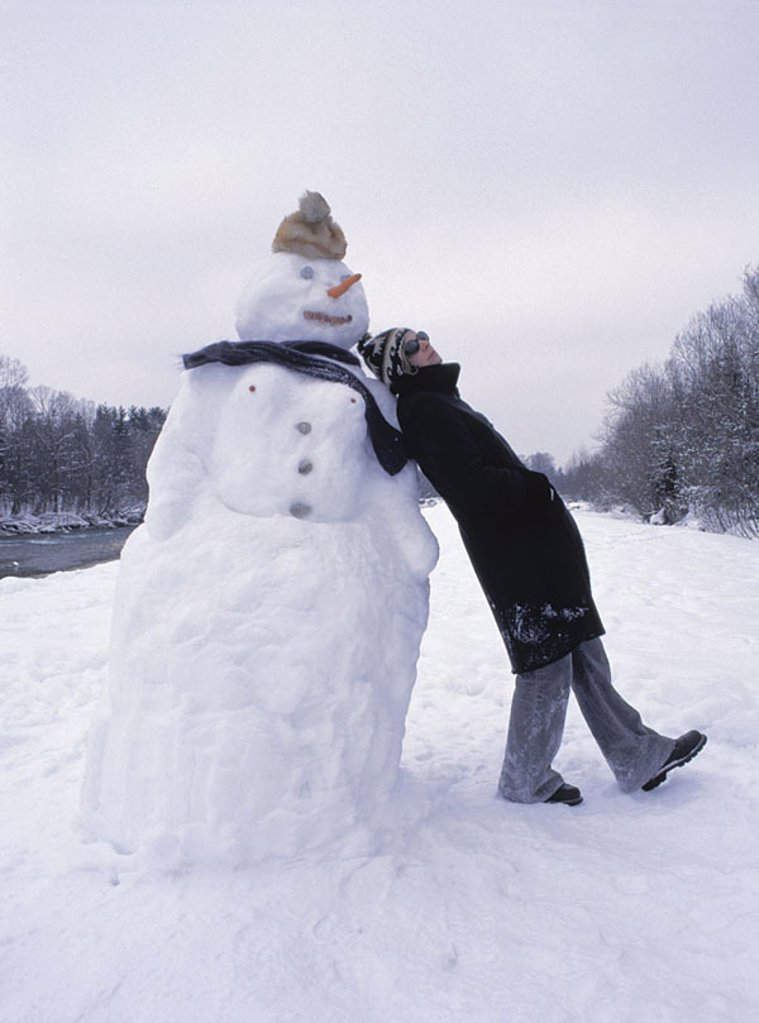 Snowman, woman, leans, at the side, people quite-bodies, winter-clothing, get along coat, cap headgear sun glass leisure time holidays, Christmas time, thought-deep, thoughtfulness, memory, childhood, dreams winter-landscape, outside, : Stock Photo