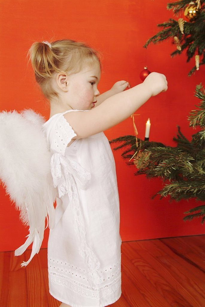 Stock Photo: 1558-119078 Christmas, child, girls, braids, little dress, angel-wings, side-opinion, ´Christmas-angels´, Christian-tree, detail, people, toddler, 2-4 years, wings, outfit, angels, little angels, stands, plays, helps, decorates, fir-tree, tree-jewelry, festively, dec