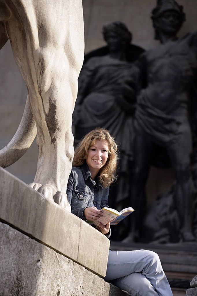Germany, Bavaria, Munich, commander-hall, lion-statue, detail, woman, young, sits, : Stock Photo