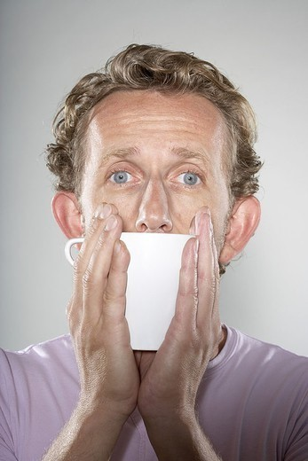 Man, middle age, coffee-cup, holds, portrait, series, people, men´s-portrait, 40-50 years, Shirt, pink, curls, sail-ears, eye-color blue, gaze camera, mouth, cup, beverage, hands, covers is warm, studio, : Stock Photo