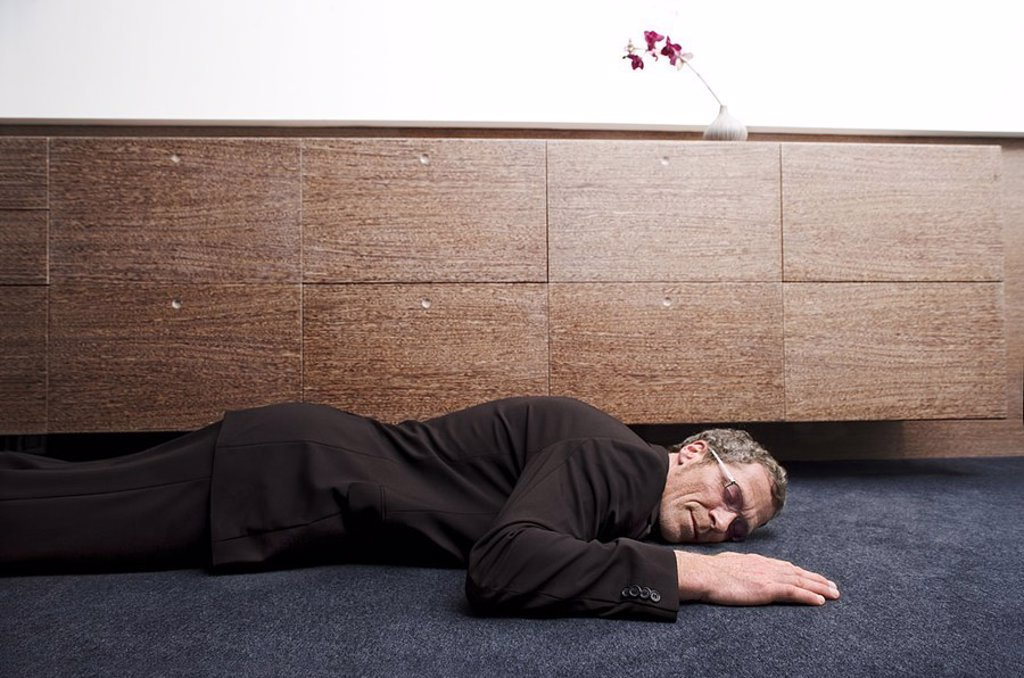 Man, suit, floor, lies, smiles, sleeps, sideboard, detail, series, people, 40-50 years, glasses, glasses-bearers, business, business-clothing, indoors, office, living, concept, recuperation, relaxation, happily, exhaustion, dreams passiveness, eyes closed : Stock Photo