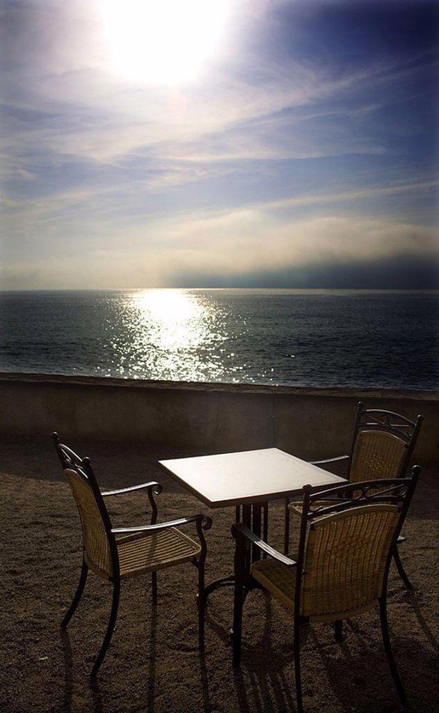 Stock Photo: 1558-126307 Terrace, table, chairs, sea-gaze, Spain, Balearen, island Majorca, Cala Ratjada, destination, tourism, loneliness, nobody, sea, Mediterranean, view, romanticism, back light, sun, pub, cafe,