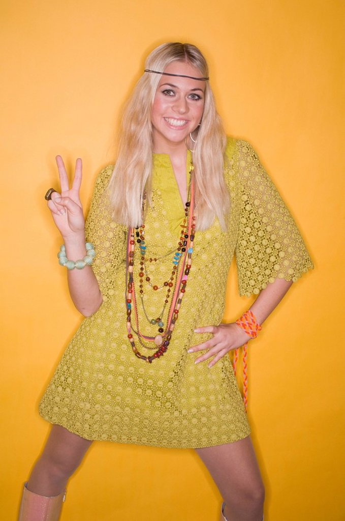 Stock Photo: 1558-132906 Woman, young, dress, jewelry, gesture, Victory signs, detail, 70er years of style, series, people, 20-30 years, blond, long-haired, mini-dress yellow, necklaces, arm-chains, fashion-jewelry, stands, signals, peaces, Peace, peace-symbol, Hippielook, hippie