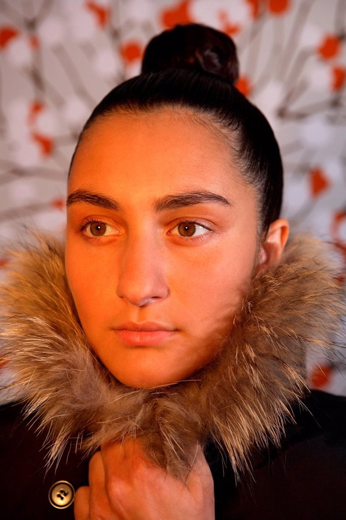 Stock Photo: 1558-134050 Woman, young, hair-knots, seriously, keeps closed winter-jacket, fur-collars, portrait, people, girls 16-20 years 20-30 years dark-haired hairdo, topknot, winter-clothing, fashion, alone drily, lonesome, lost in thought, wallpaper, wallpaper-pattern, inte