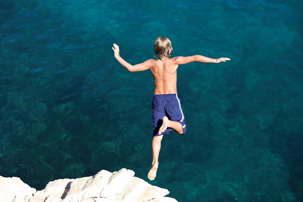 Stock Photo: 1558-134687 lake, rocks, boy, Klippenspringen, back view, series, people, child, swim-suit, trunks, blue, full-length, rocks, coast, vacation, vacation, fun, courage, overcoming, height, cliffs, jumps, swims, swims, daring, water,