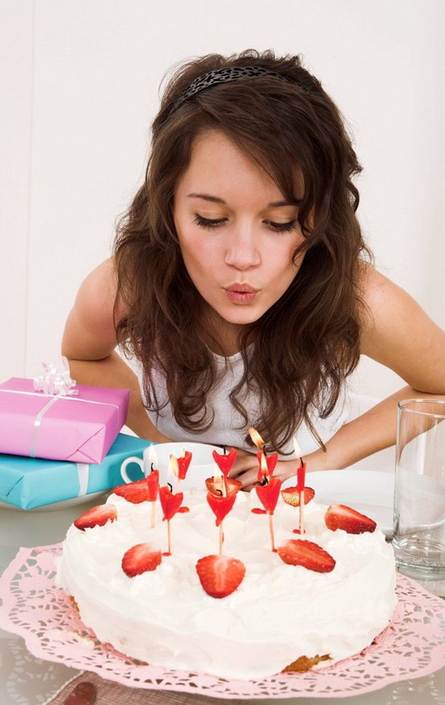 Stock Photo: 1558-136499 girl, pie, candles, blows out, gifts, semi-portrait, table, people, teenagers, teenager-girl, cream-pie, strawberry-pie, birthday-pie, cakes, decorates, decorates, lovingly, strawberries, duckies, birthday-candles, burns, blows out, blows, wish, surprise,