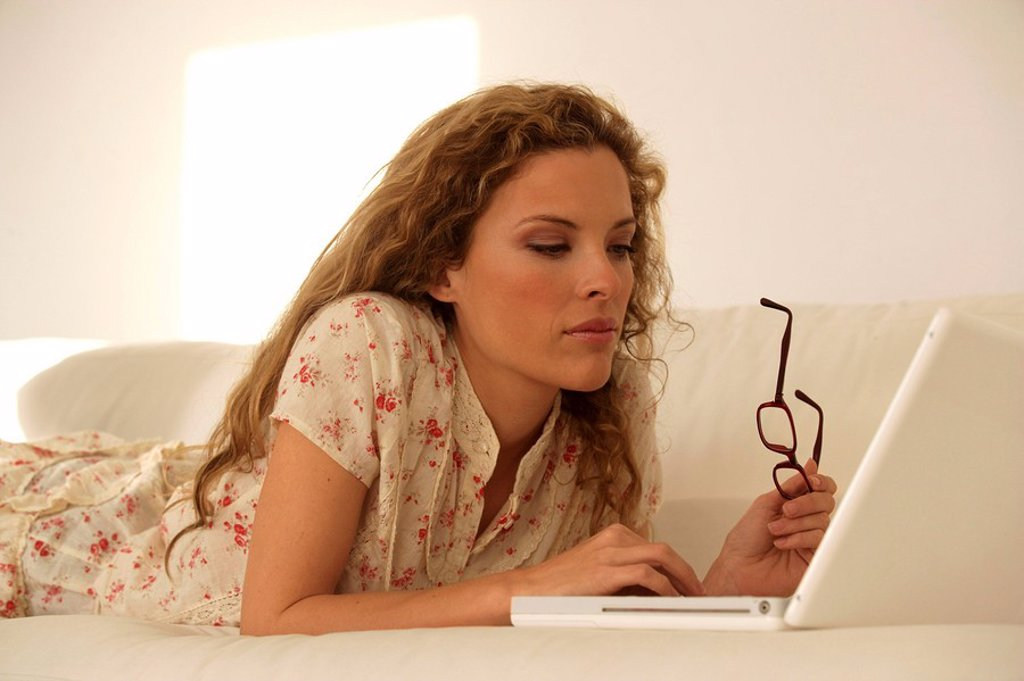 Stock Photo: 1558-137143 Sofa, woman, young, laptop, concentration, detail, series, people, blond, long-haired, curls, lie, comfortable, casual, computers, data input, data-retrieval, wireless, internet, surf the web, mailing, Chatten, telecommunication, information, interest, sy. Sofa, woman, young, laptop, concentration, detail, series, people, blond, long-haired, curls, lie, comfortable, casual, computers, data input, data-retrieval, wireless, internet, Internetsurfen, Mailen, Chatten, telecommunication, information,
