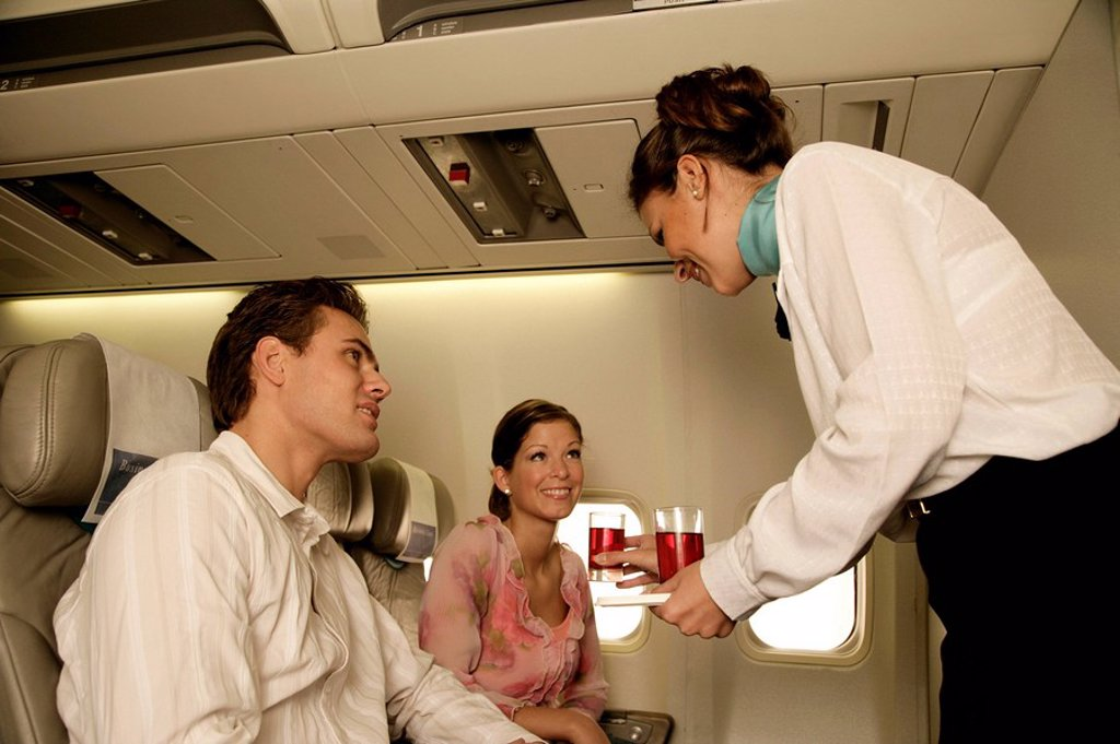 Stock Photo: 1558-144077 Airplane, couple, young, flight_trip, stewardess, kindly, services, beverage,