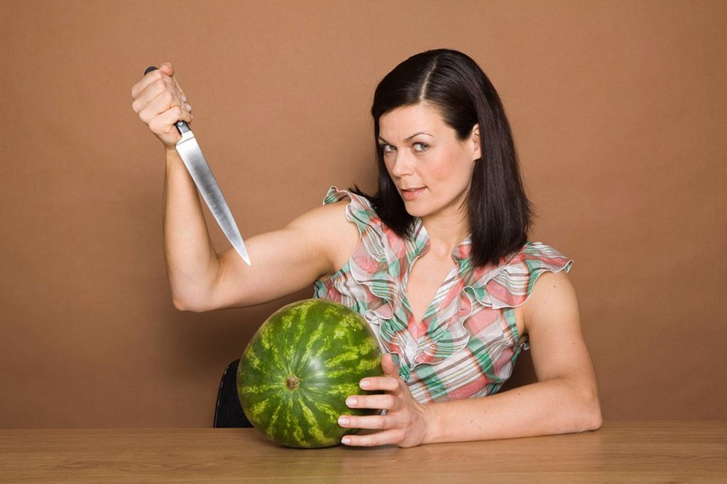 woman, brunette, gesture, knives, melon, portrait, series, people, woman_portrait, 30_40 years, long_haired, cozy, overweight, expression, kitchen_knives, fruit, fruit, watermelon, brags, background brown, : Stock Photo