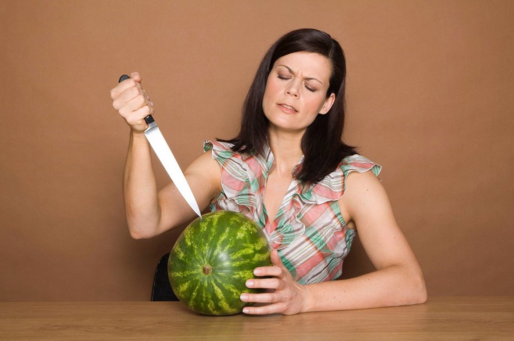 Stock Photo: 1558-147953 woman, brunette, gesture, knives, melon, portrait, series, people, woman_portrait, 30_40 years, long_haired, cozy, overweight, expression, kitchen_knives, fruit, fruit, watermelon, brags, background brown,