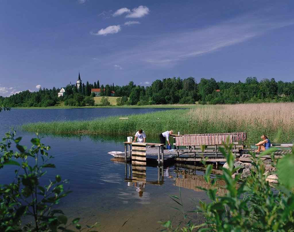 Stock Photo: 1558-150906 Finland, Ristijna, lake,bridge, women, carpets, summer, cleans waters, wood_bridge boat_bridge landscape, village church, forest, reed, people, Fleckerlteppiche, laundry, hand_laundry, cleaning, cleans, housework, house clean, outside,